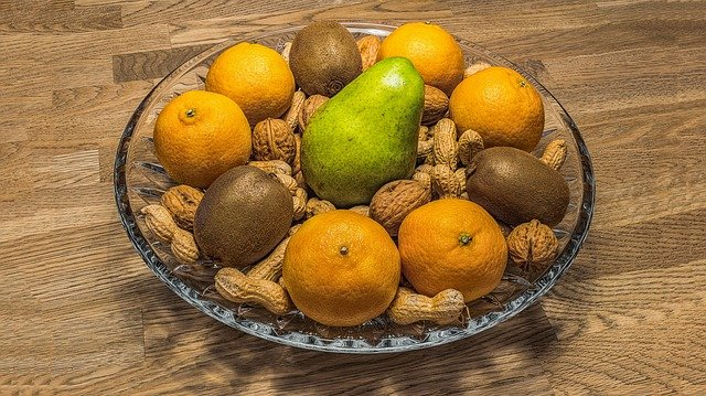 A bowl of fruit sitting on top of a wooden table