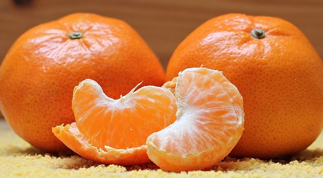 Two oranges sitting on top of a table